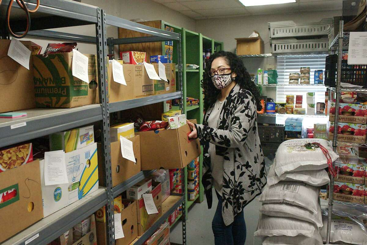 Sarah's House program director Veronica Rodriguez stands near boxes ready to be distributed daily to needy families who live in the community. The pantry needs donations of food, masks and cleaning supplies.