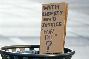 A sign sits in a trashcan during a peaceful protest against police brutality and racism on June 6 in Dallas, Texas. On May 25, 2020, Floyd, a 46-year-old black man suspected of passing a counterfeit $20 bill, died in Minneapolis after Derek Chauvin, a white police officer, pressed his knee to Floyd's neck for almost nine minutes. (Photo by Cooper Neill/Getty Images)