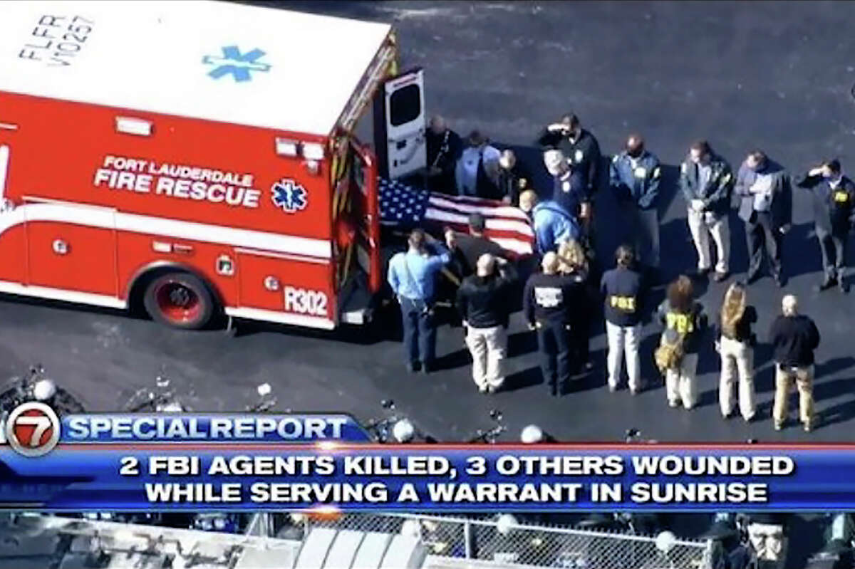 Law enforcement officers load a casket into a vehicle, Tuesday, Feb. 2, 2021, in Sunrise, Fla. Two FBI agents were fatally shot and three wounded while trying to serve a search warrant in Florida on Tuesday, prompting a SWAT team to storm an apartment building where the suspect was holed up as neighbors huddled inside their homes.