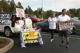 Donna Jones (middle right) has signs around her desk and car in the parking lot of K-mart to collect signatures recalling governor Gavin Newsom on Saturday, Sept. 26, 2020, in Grass Valley, Calif. At right is Michael Grover Coltharp II running for governor.
