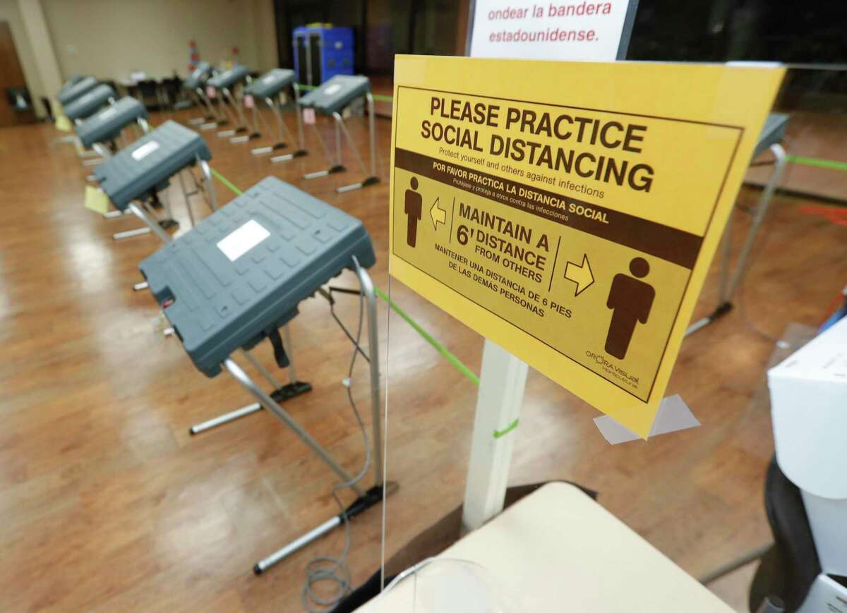 A sign encourages proper social distancing at the South Montgomery County Community Center, Thursday, July 2, 2020, in The Woodlands. Election officials have implemented several safety and sanitization features to protect voters and polling location volunteers from the coronavirus.