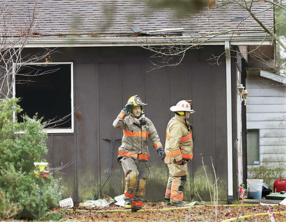 Firefighters walk around the house at 6507 Alpha Drive in rural Fosterburg Monday morning where children told firefighters about a blaze inside. Late Tuesday police were seeking Andre Darnell Mathis, 34, of Alton, on charges of aggravated arson, armed violence, child pornography, aggravated domestic battery and indecent solicitation of a child.