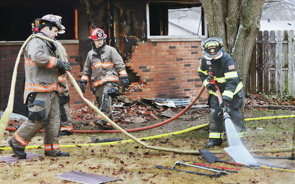 """A firefighter washes equipment Monday morning after a fire at a home in the 2300 block of Wedgewood Avenue in Godfrey that left two people dead, Robert B. Andrews, 59, and Leonard """"James"""" Ebrey, 67. Police believe the two died in a double homicide."""