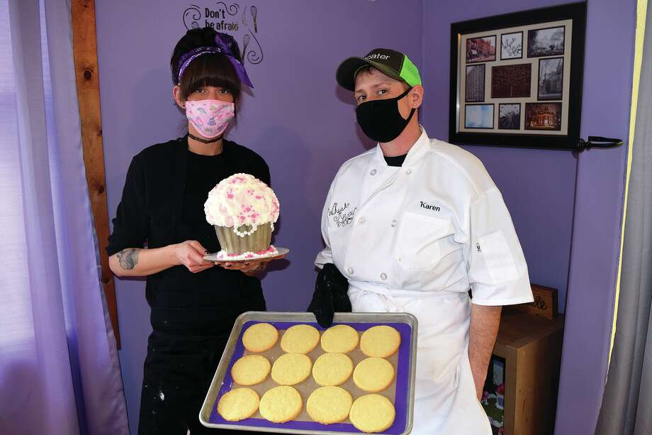 Anastasia (left) and Karen Bergner-McNeece hold some of their baked treats — freshly made sugar cookies and a giant cupcake. Photo: Rochelle Eiselt, Journal-Courier