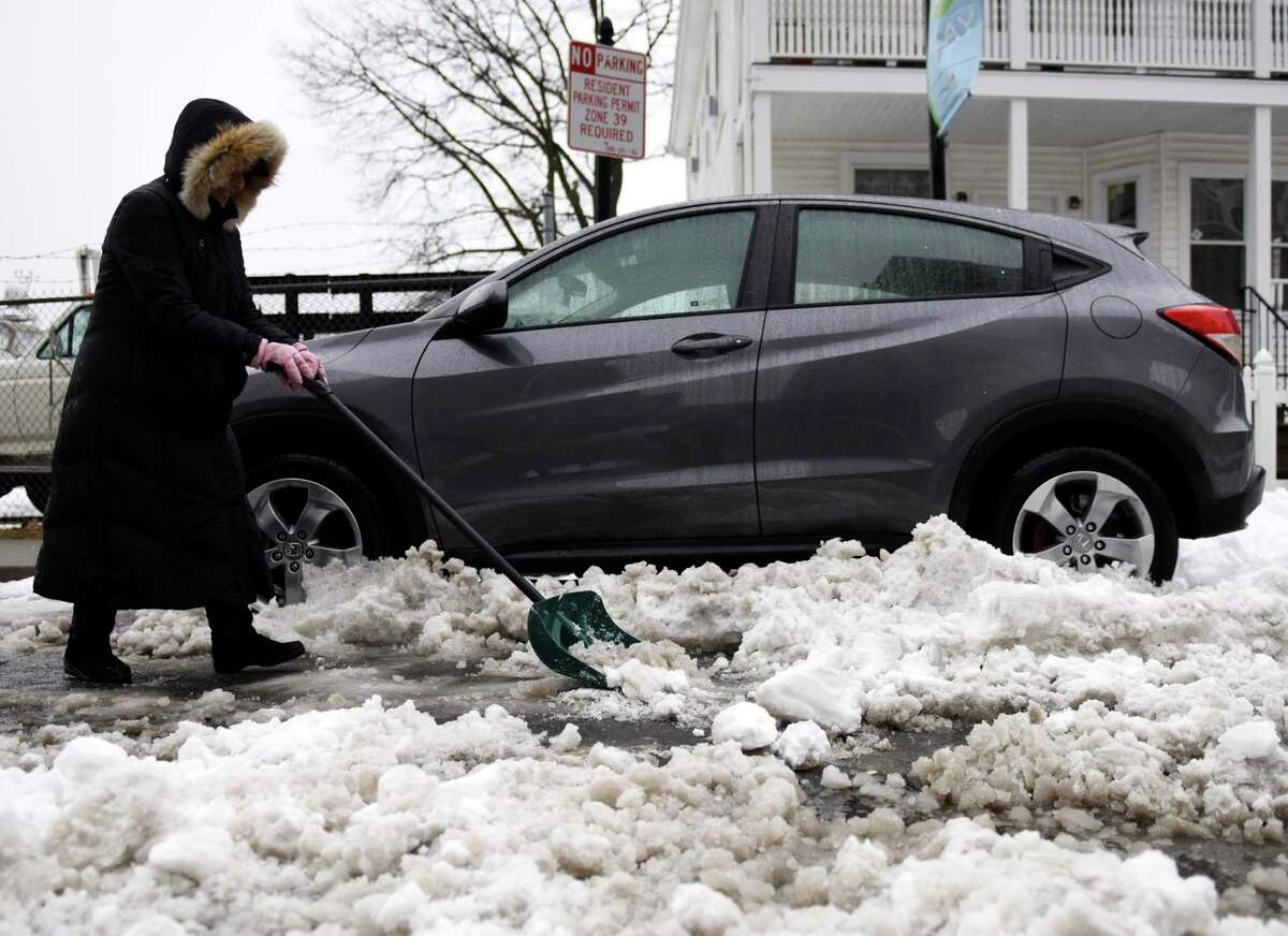 Elizabeth Zamora digs out her car from a pile of snow in the South End of Stamford on Tuesday. Stamford spent Tuesday digging out after more than a foot of snow fell over the course of Sunday evening through Tuesday morning.