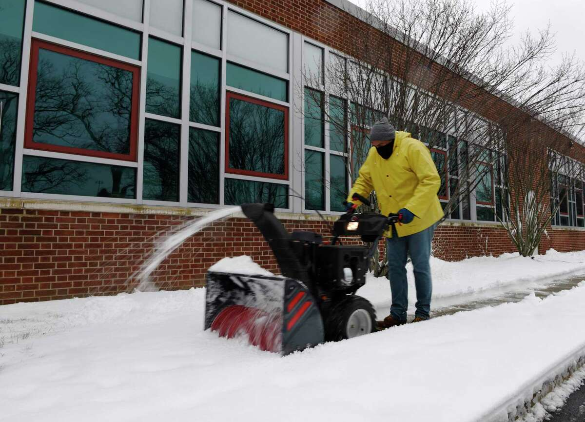 A man clears snow from the front of J.M. Wright Technical High School in Stamford on Tuesday. Stamford spent Tuesday digging out after more than a foot of snow fell over the course of Sunday evening through Tuesday morning.