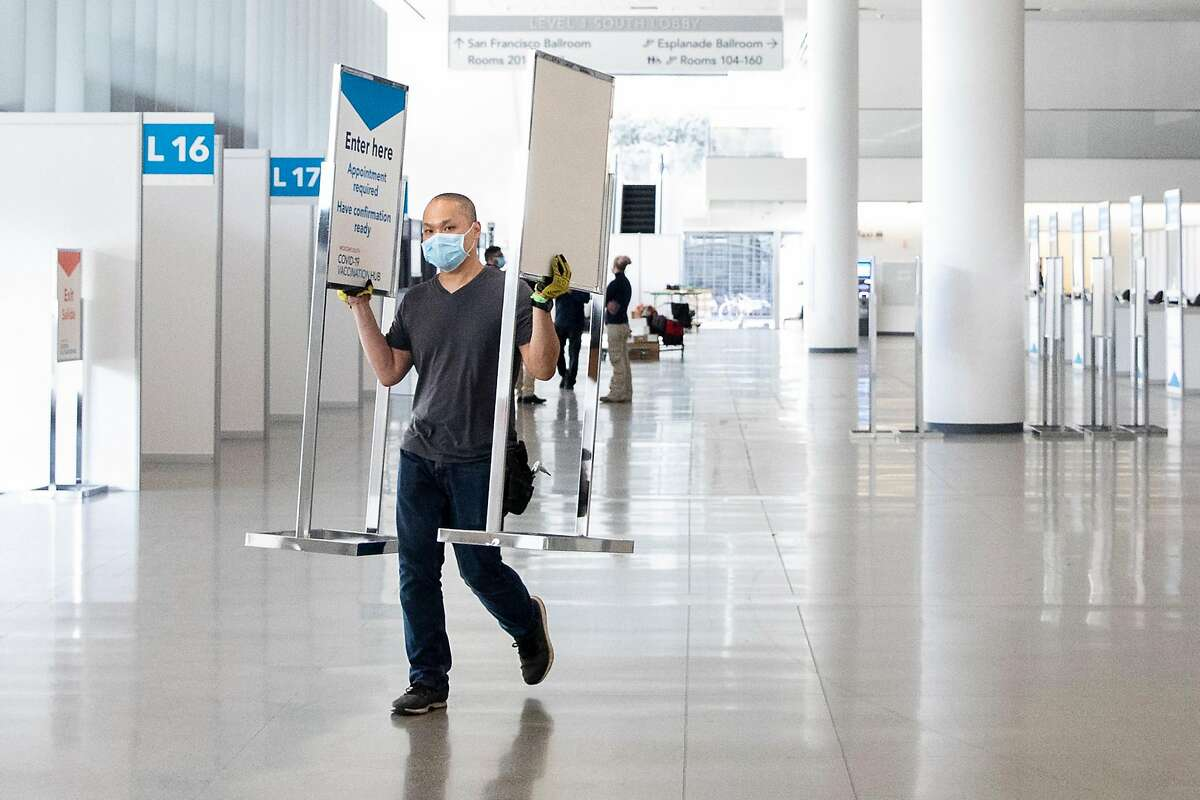 A city worker moves signage while working to prepare a mass COVID-19 vaccination site at Moscone South in San Francisco.