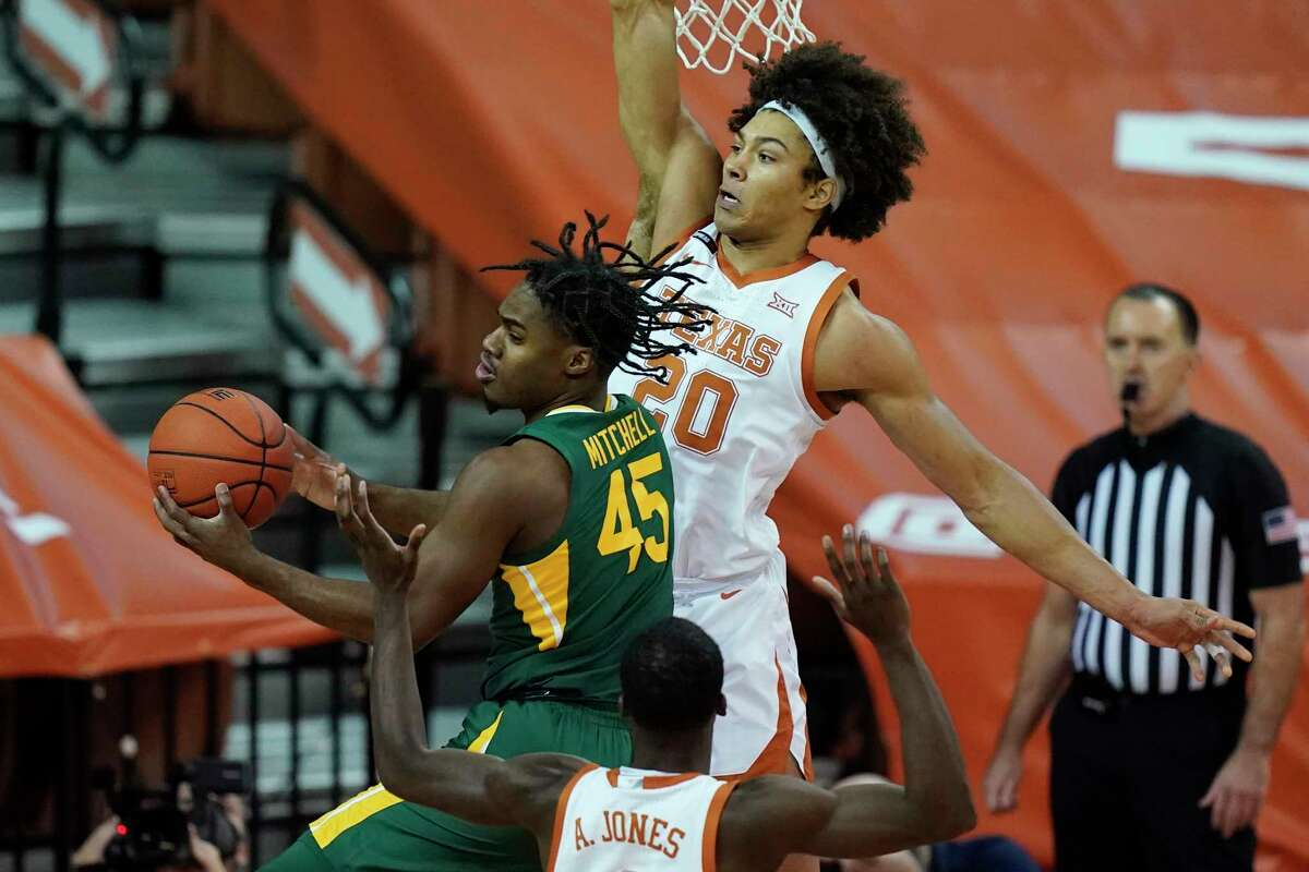 Baylor guard Davion Mitchell (45) is defended by Texas forward Jericho Sims (20) as he drives to the basket during the first half of an NCAA college basketball game Tuesday, Feb. 2, 2021, in Austin, Texas. (AP Photo/Eric Gay)