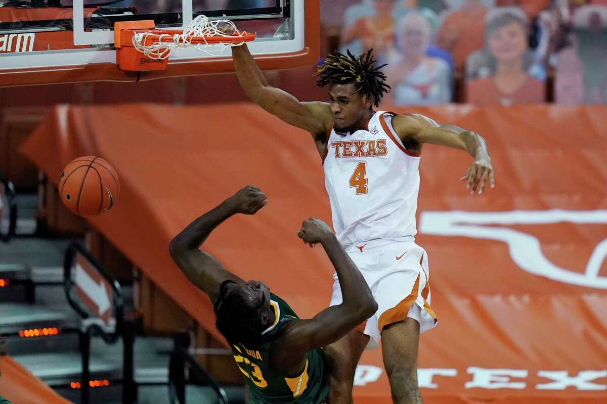 Texas forward Greg Brown (4) scores over Baylor forward Jonathan Tchamwa Tchatchoua (23) during the second half of an NCAA college basketball game Tuesday, Feb. 2, 2021, in Austin, Texas. (AP Photo/Eric Gay)