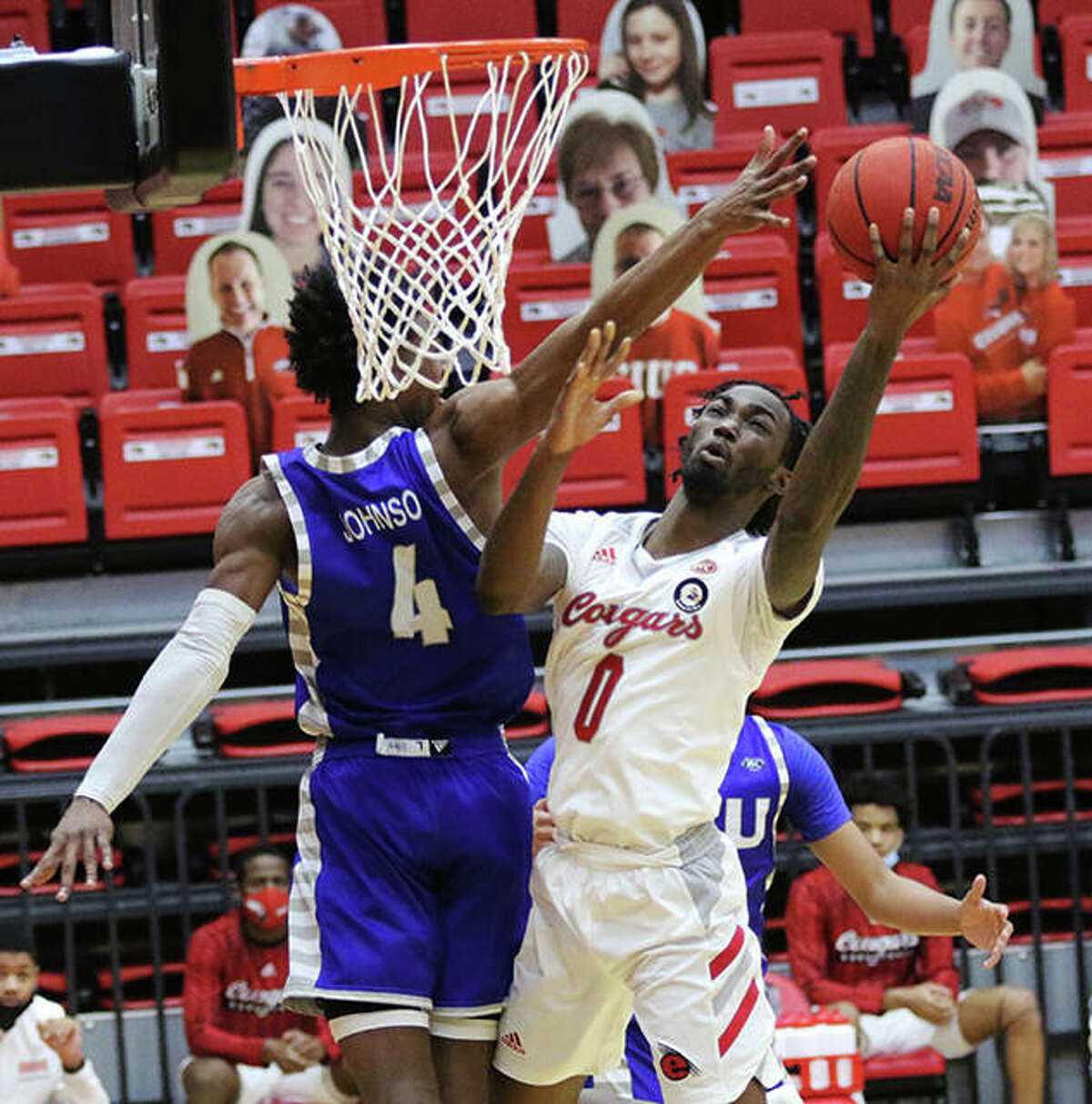 SIUE's Sidney Wilson (0) takes the ball the rim and scores while Eastern Illinois' Marvin Johnson defends Tuesday at First Community Arena in Edwardsville.