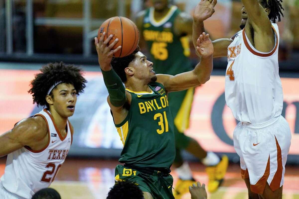 Baylor guard MaCio Teague (31) drives to the basket against Texas forward Greg Brown (4) during the second half of an NCAA college basketball game, Tuesday, Feb. 2, 2021, in Austin, Texas. (AP Photo/Eric Gay)
