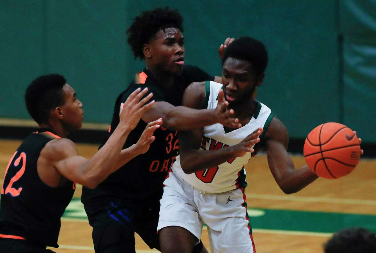 The Woodlands guard David Omokwale (0) looks to pass under pressure from Grand Oaks guard Sean Stewart (12) and center Vincent Caccanza (42) during the third quarter of a District 13-6A high school basketball game at The Woodlands High School, Tuesday, Feb. 2, 2020, in The Woodlands.