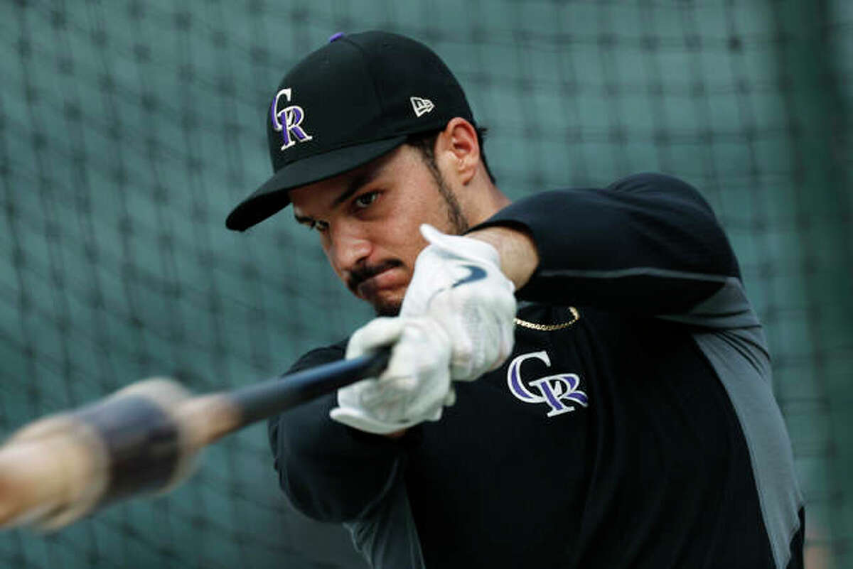 In this Friday, Sept. 27, 2019, file photo, Colorado Rockies third baseman Nolan Arenado warms up before a baseball game against the Milwaukee Brewers in Denver.