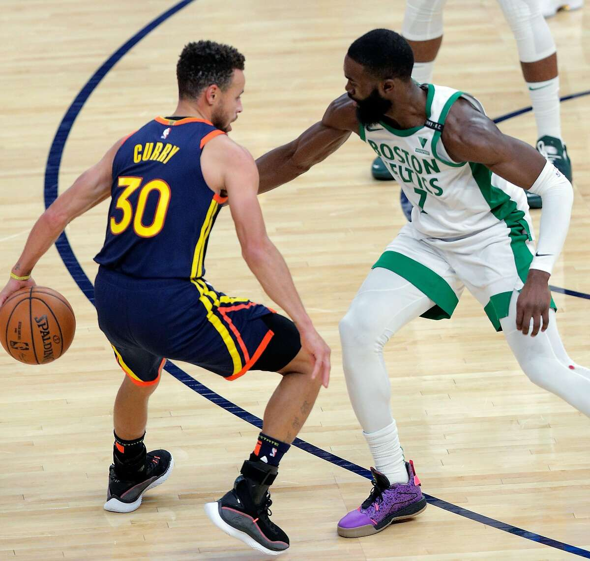 Stephen Curry (30) dribbles behind his back as he drives to the basket against Jaylen Brown (7) in the first half as the Golden State Warriors played the Boston Celtics at Chase Center in San Francisco, Calif., on Tuesday, February 2, 2021.