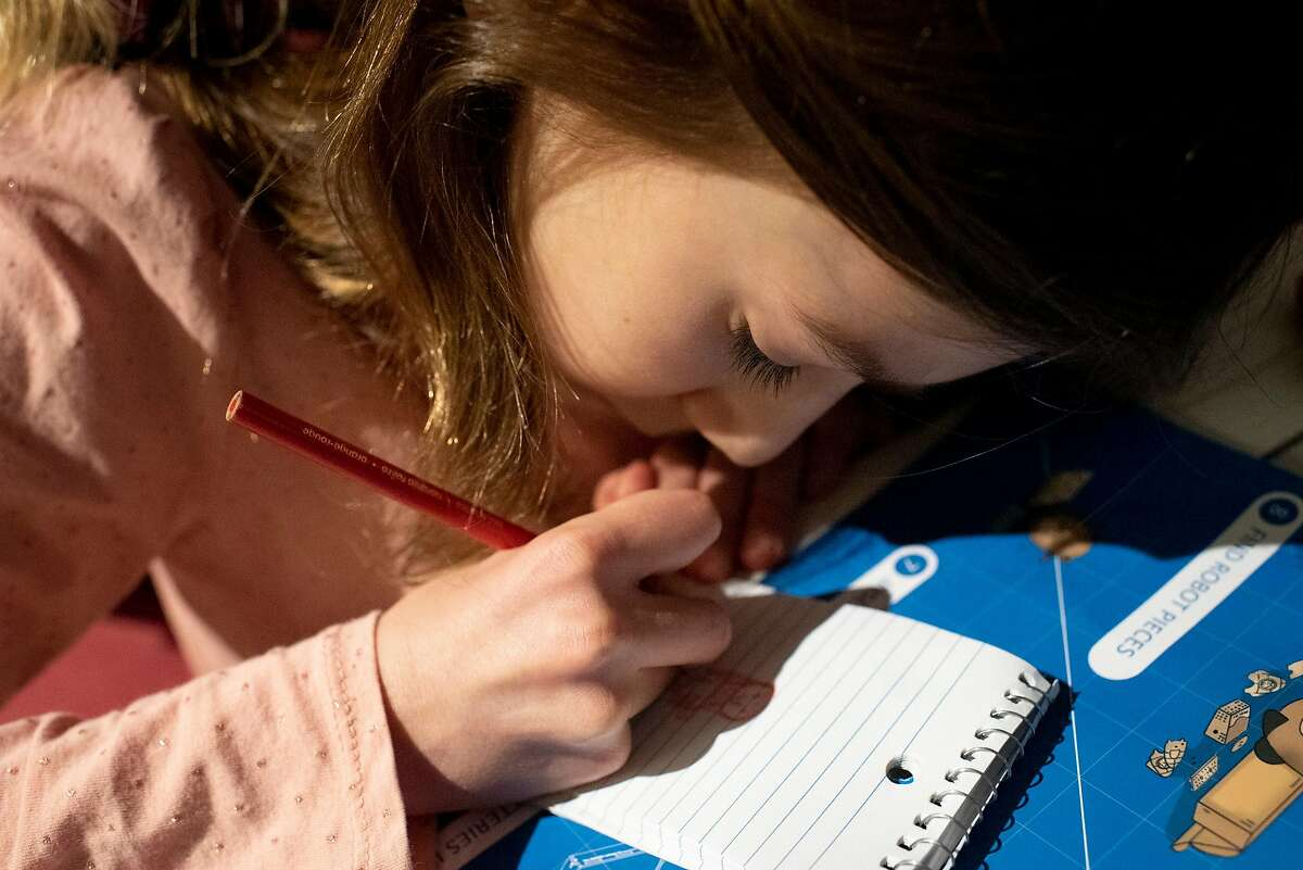 Vardeni Vardanyan, 8, a second-grader at Marshall Elementary School, draws in the evening at her Mission Bay apartment in San Francisco, Feb 2, 2021.