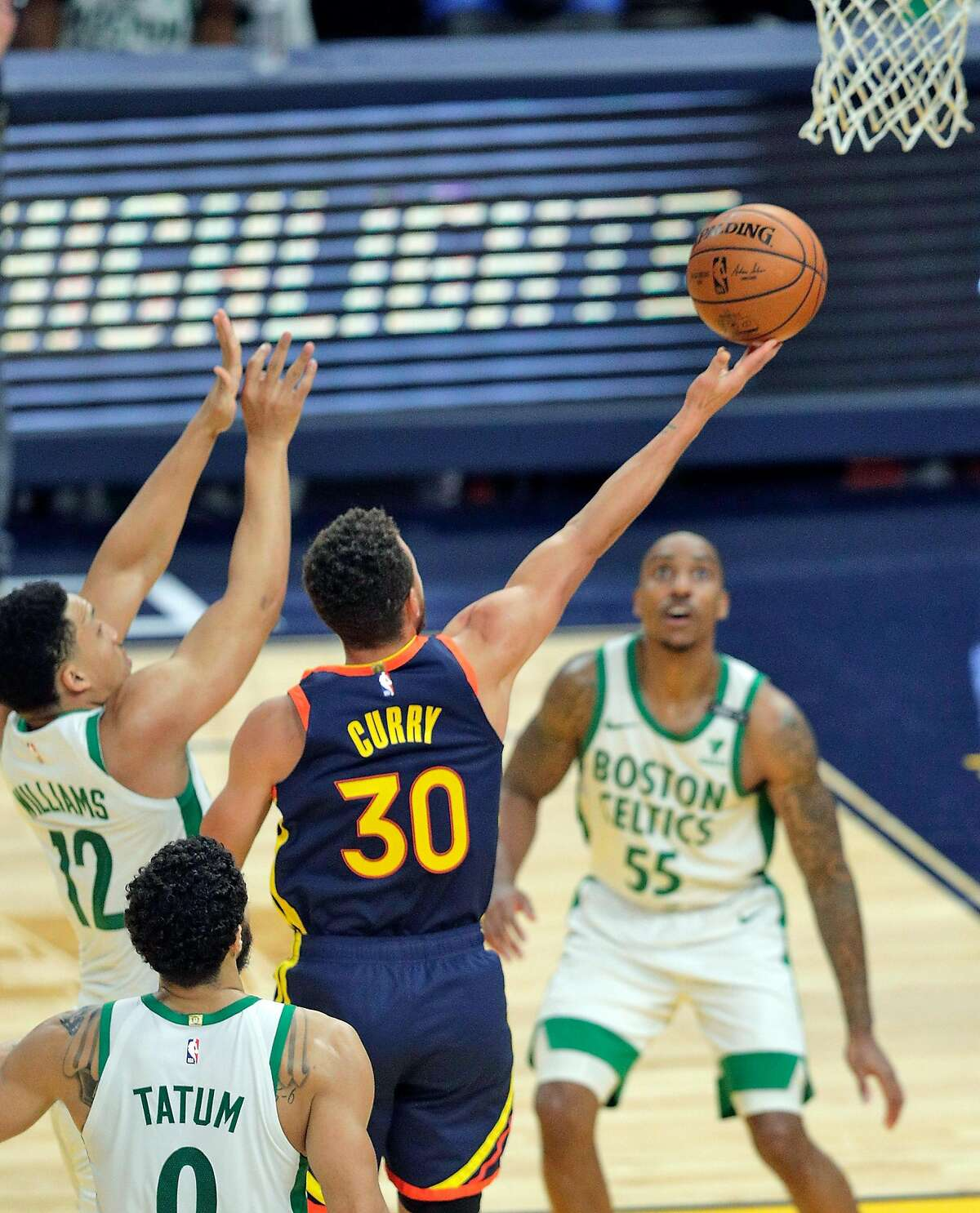 Stephen Curry, who scored 38 points, puts up a shot between Boston's Grant Williams and Jeff Teague (55).