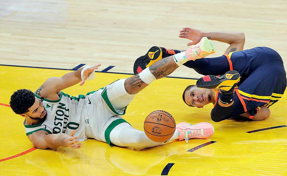 Juan Toscano Anderson (95) gets tangles up with Jayson Tatum (0) chasing a loose ball late in the fourth quarter before the Golden State Warriors were defeated 111-107 by the Boston Celtics at Chase Center in San Francisco, Calif., on Tuesday, February 2, 2021.