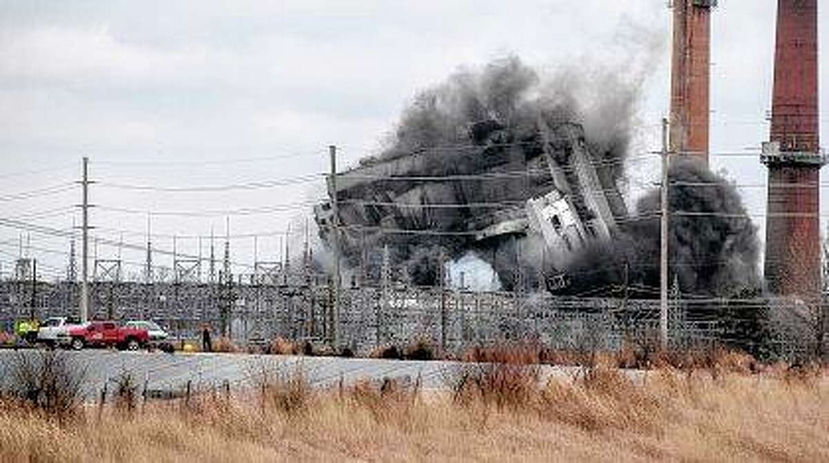 Workers watch from a safe distance Monday as the main structure of the former Wood River Power Plant in East Alton is brought down by explosives. Three smoke stacks that some Madison County residents are concerned about were not part of the demolition at the former Dynegy coal-fired power plant.