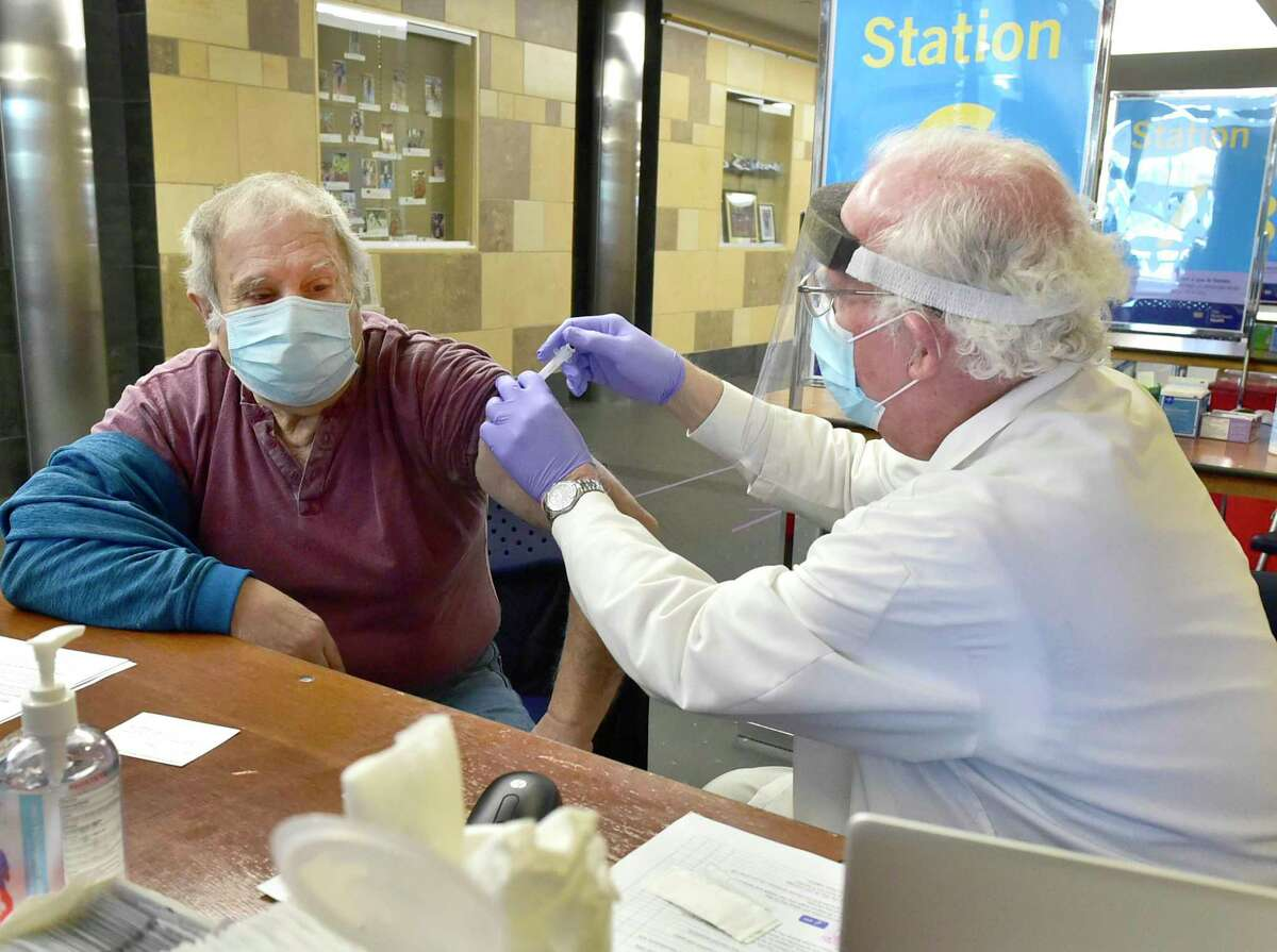 FILE PHOTO: Rocco Totino, 77, of Wallingford, left, gets his Covid-19 vaccination from Dr. Leo M. Cooney, Jr., as Yale New Haven Health and the city of New Haven have opened a vaccination center last month.