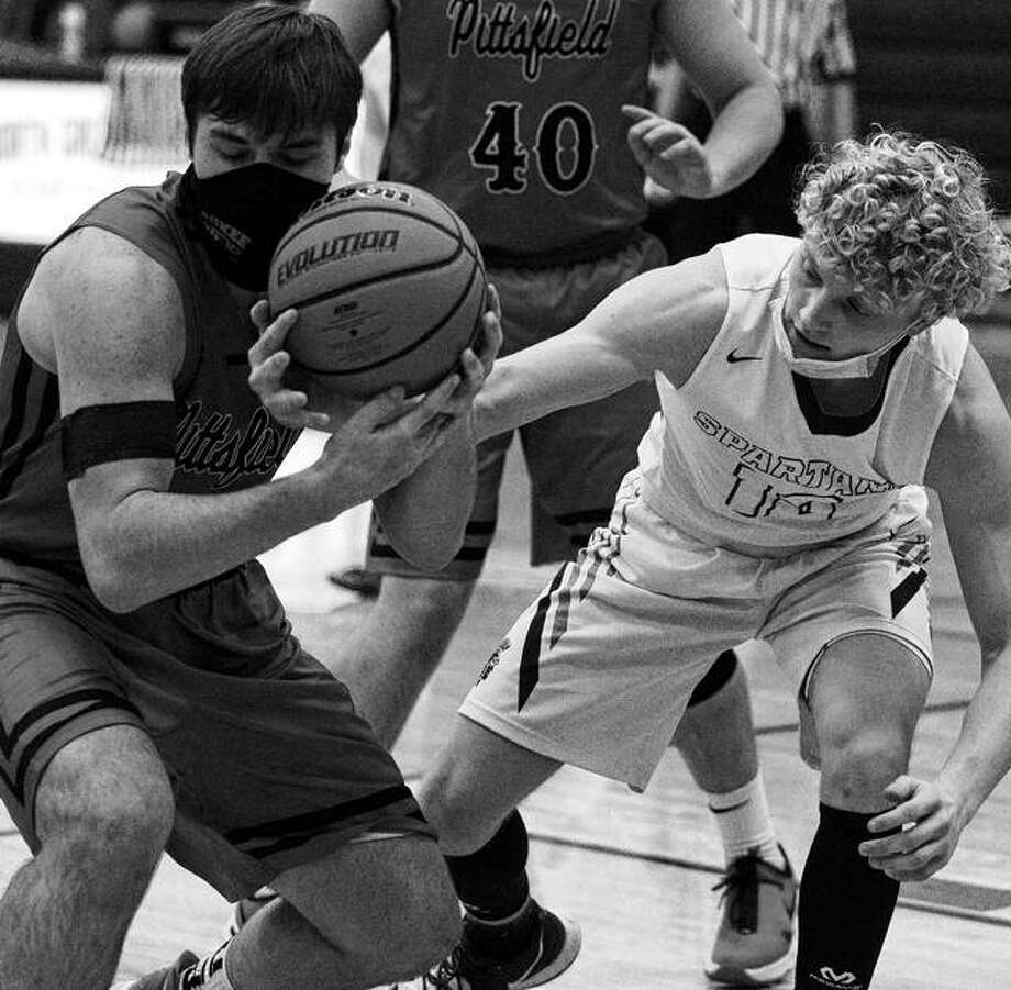 North Greene's Levi Ballard reaches in on Pittsfield's Carter Klatt during a varsity boys' basketball game at White Hall Tuesday night. Photo: Dennis Mathes, Journal Courier | For The Telegraph