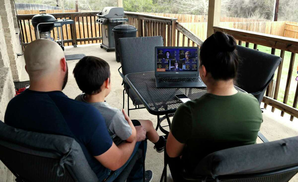 Amanda Flores attends the SA Virtual School Fair on Saturday to research possible schools for her child, Jaxson Flores, 6, being held by father Jason Flores at their home on Saturday