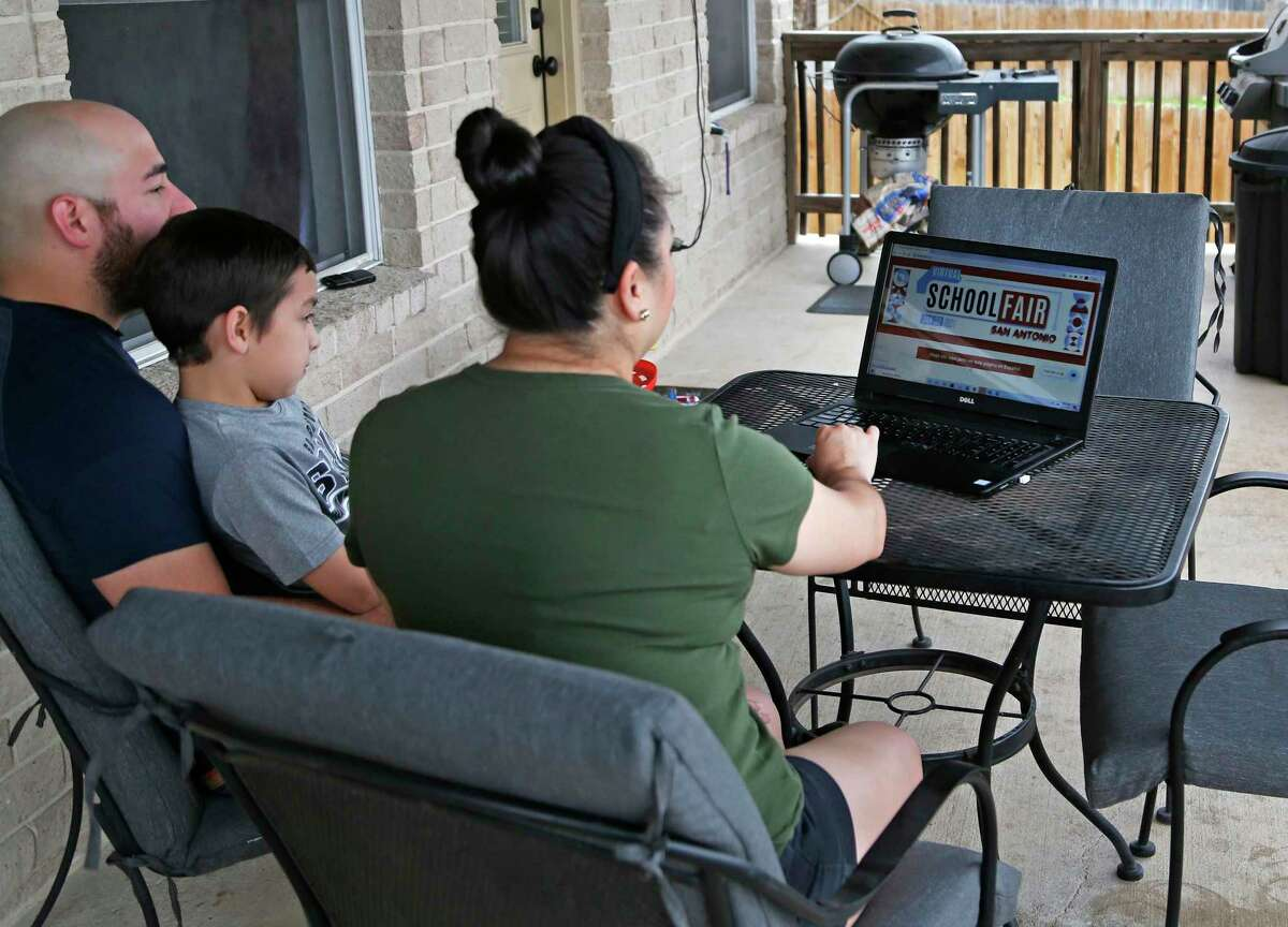 Amanda Flores attends the SA Virtual School Fair on Saturday to research possible schools for her child, Jaxson Flores, 6, being held by father Jason Flores at their home on Saturday.
