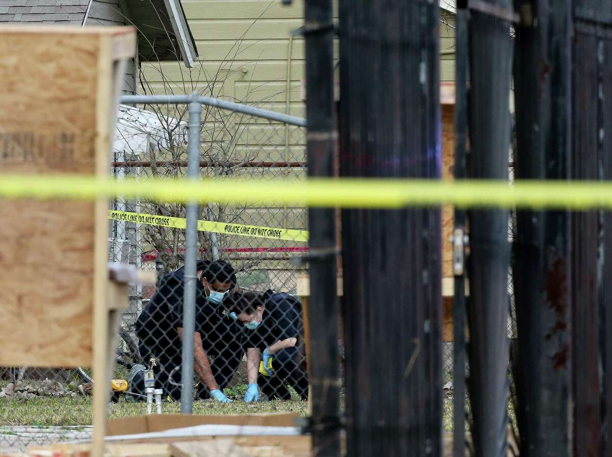 Houston Police officers investigate the scene of a police shooting on the 100 block of East 44th Street on Monday, Jan. 25, 2021, in Houston. An officer shot a man suspected in a fatal shooting on the 8500 block of North Main Street.