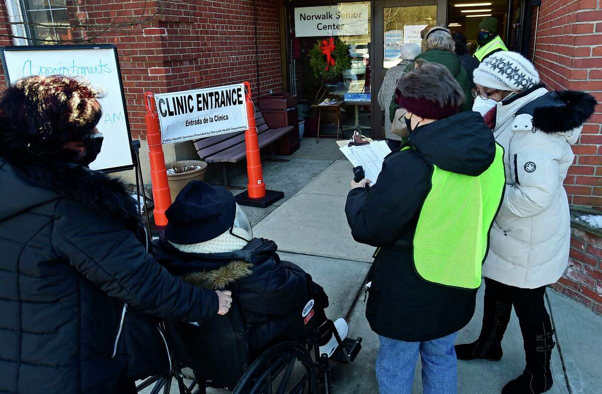 Local residents line up for their COVID vaccine Saturday, January 30, 2021, at the Norwalk Senior Center in Norwalk, Conn.