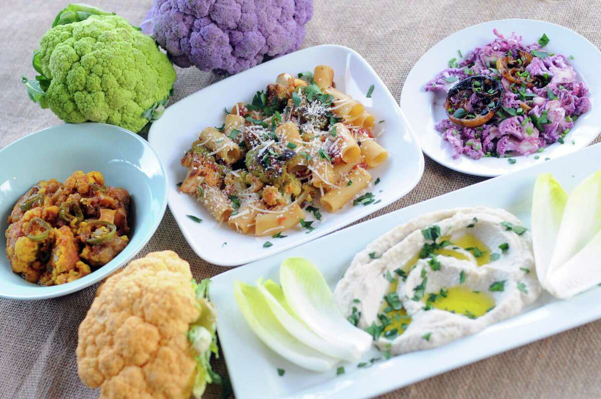 A selection of dishes made with colorful varieties of cauliflower including, clockwise from left, Spicy Cauliflower with Tomato Sauce, Pasta with Roasted Cauliflower, Shaved Purple Cauliflower Salad and Creamy Cauliflower Dip.