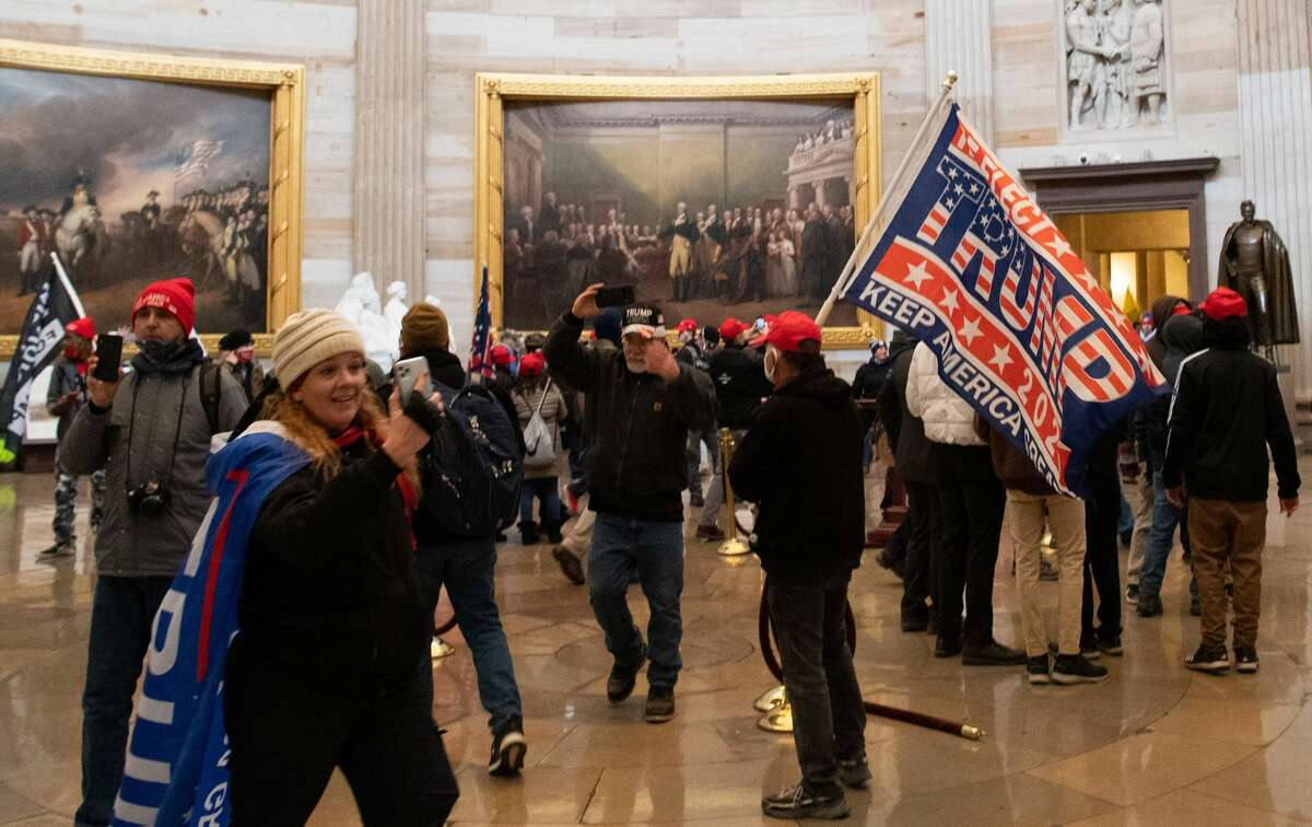 Supporters of US President Donald Trump enter the US Capitol's Rotunda on January 6, 2021, in Washington, DC. Jenny Cudd, left, can be seen inside the building wearing a Trump flag as a cape and holding her phone.
