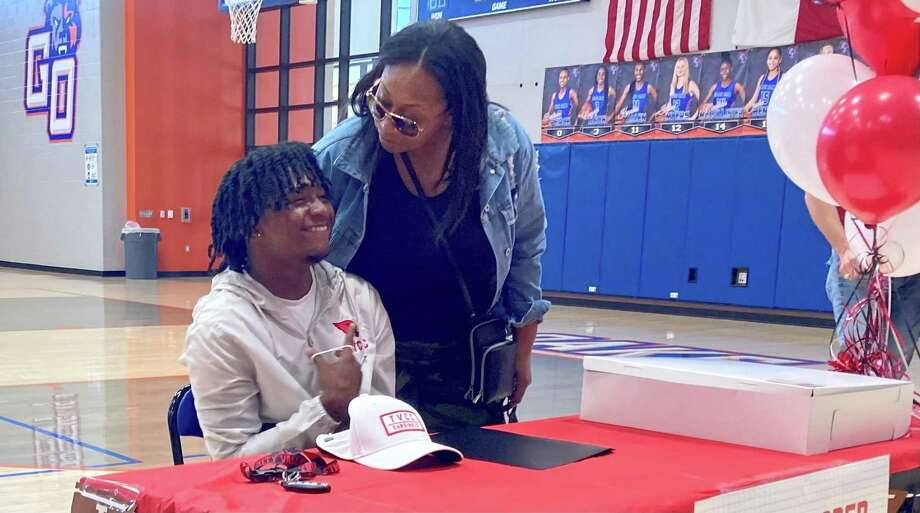 Micah Cooper, left, smiles as he poses for a photo at a National Signing Day ceremony at Grand Oaks High School on Feb. 3, 2021, in Spring, Texas. Photo: Justin Maskulinski / Staff Writer