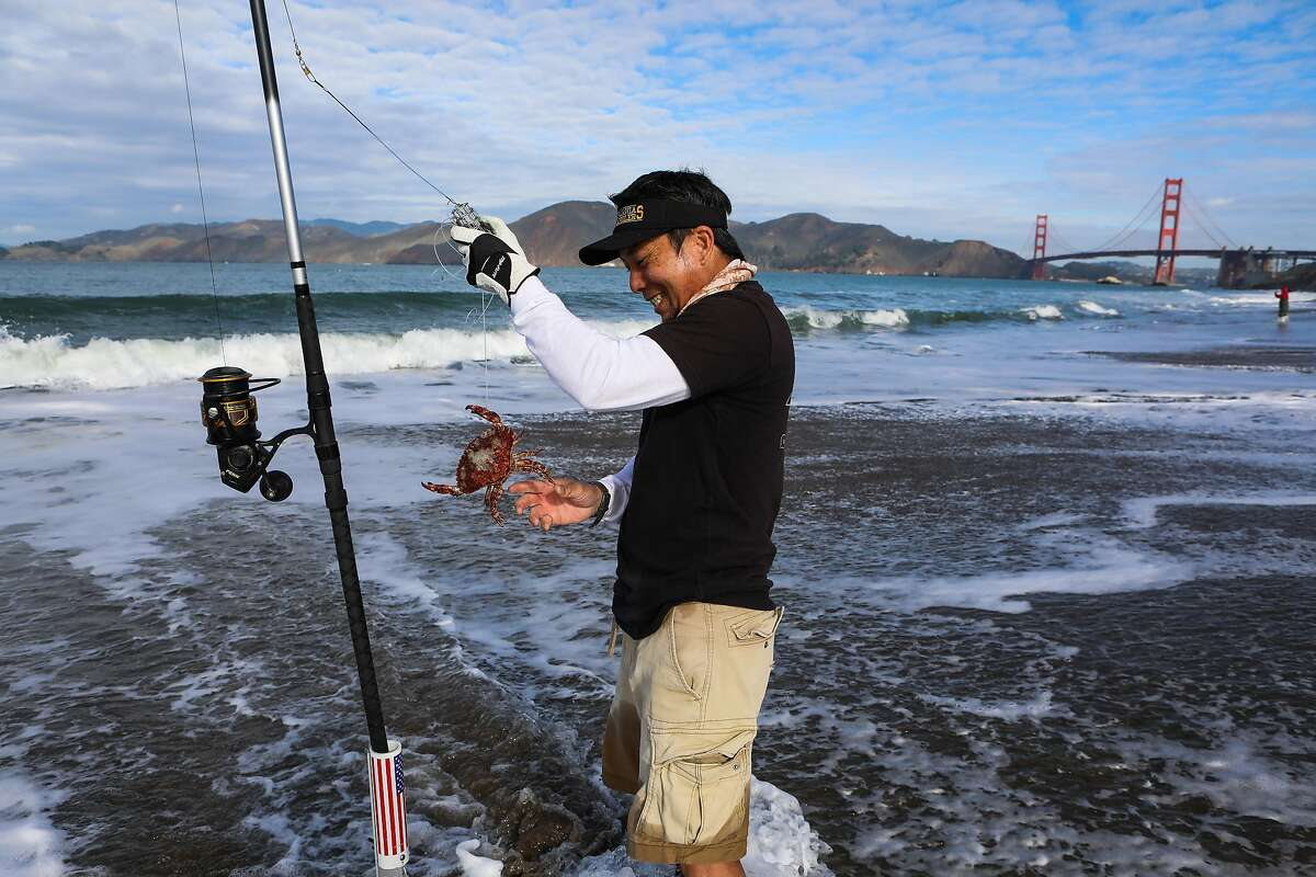 Robert Nguyen fishes for Dungeness crabs at San Francisco's Baker Beach. Sports crab fishing has been more popular than ever during the pandemic, but a favorite spot for it in the Bay Area, the Pacifica Pier, has been closed for several weeks after storms damaged it.