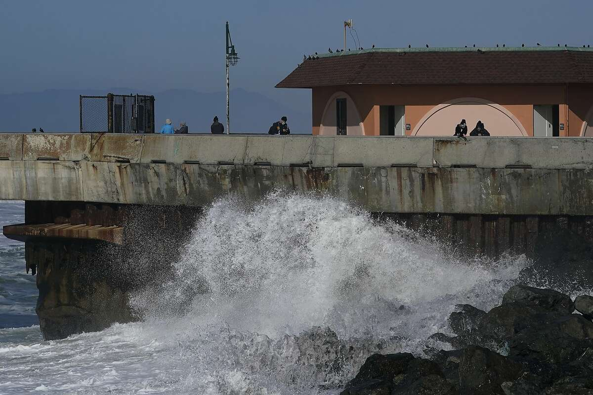 People watch as waves crash below Pacifica Pier on Jan. 11.