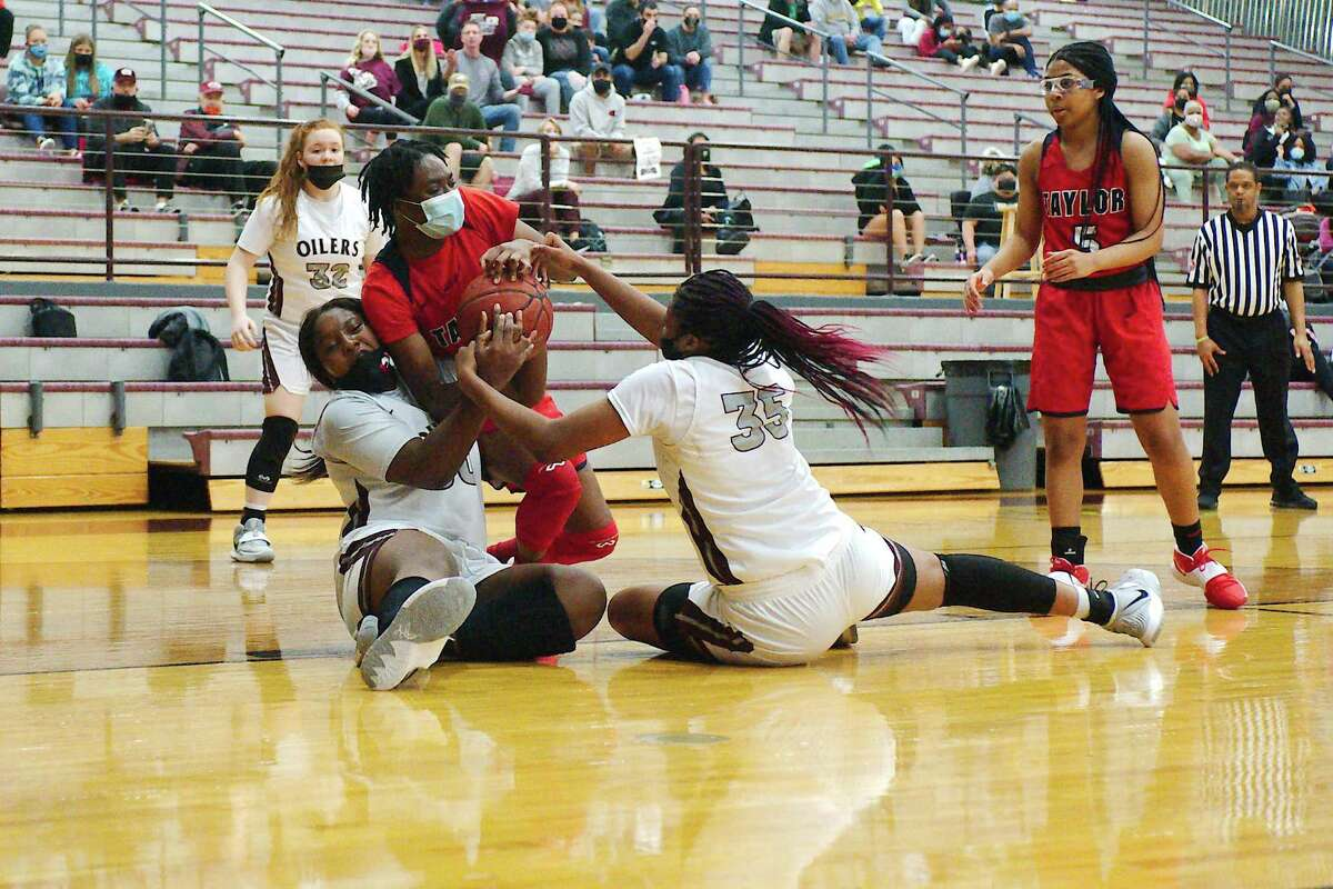 Pearland's La'niah Thornton (30), Aryelle Stevens (35) and Alief Taylor's Stephanie Osazuwa (15) fight for a loose ball Tuesday at Pearland High School.