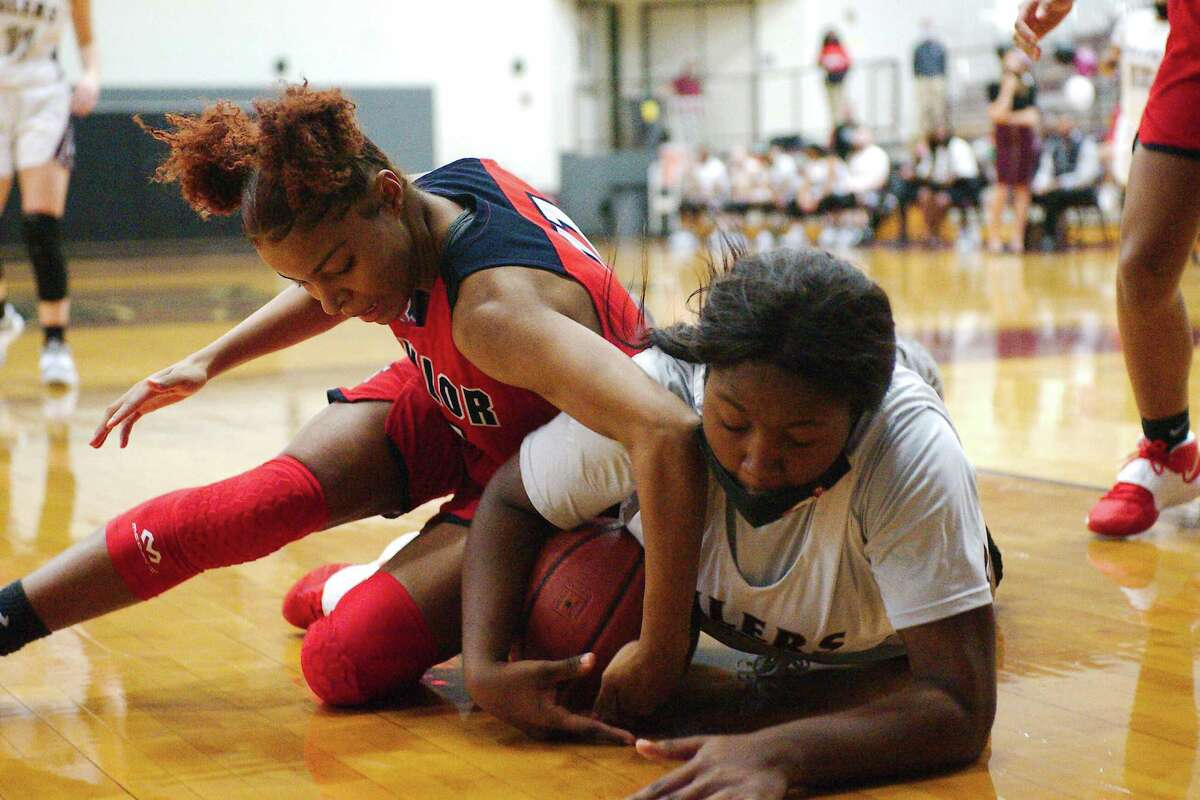 Alief Taylor's Alyssa Prier (11) and Pearland's La'niah Thornton (30) fight for a loose ball Tuesday at Pearland High School.