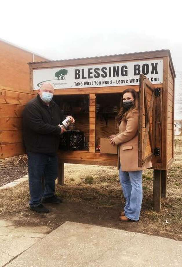 Wood River Councilman Mike Anderson, left, and state Sen. Rachelle Crowe take canned goods to the Wood River Public Library's Blessing Box.