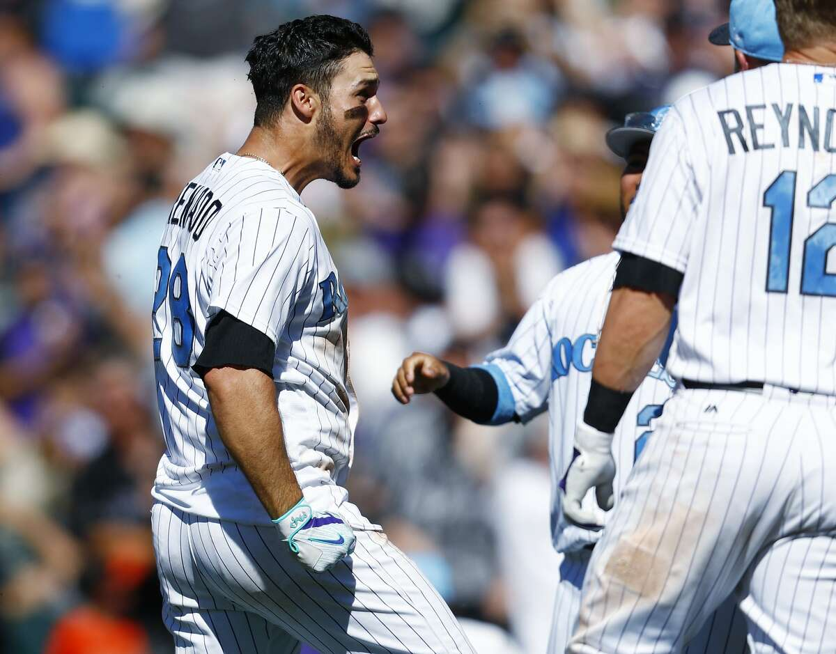 Colorado Rockies' Nolan Arenado, left, celebrates his three-run, walkoff home run with teammates in the ninth inning of a baseball game against the San Francisco Giants, Sunday, June 18, 2017, in Denver. The Rockies won 7-5.