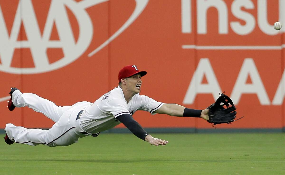 Texas Rangers center fielder Drew Robinson leaps to catch a fly-out by Detroit Tigers' John Hicks in the first inning of a baseball game, Monday, Aug. 14, 2017, in Arlington, Texas.