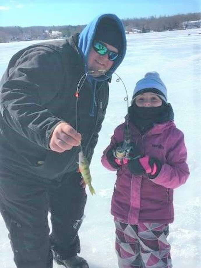 During last year's Portage Lake Ice Fun Fish, Julia Noury (right), of Quebec, caught a perch. (News Advocate file photo)