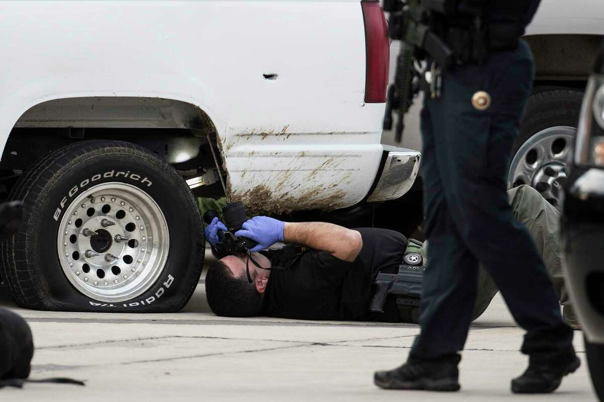 Law enforcement officers investigate a vehicle allegedly involved in an officer-involved shooting near I-45 and Rayford Road on Wednesday, Feb. 3, 2021 in Spring. Following the incident, a manhunt followed Wednesday after two people fled the scene of an officer-involved shooting. The incident was reported at about 1:40 p.m. in the area.