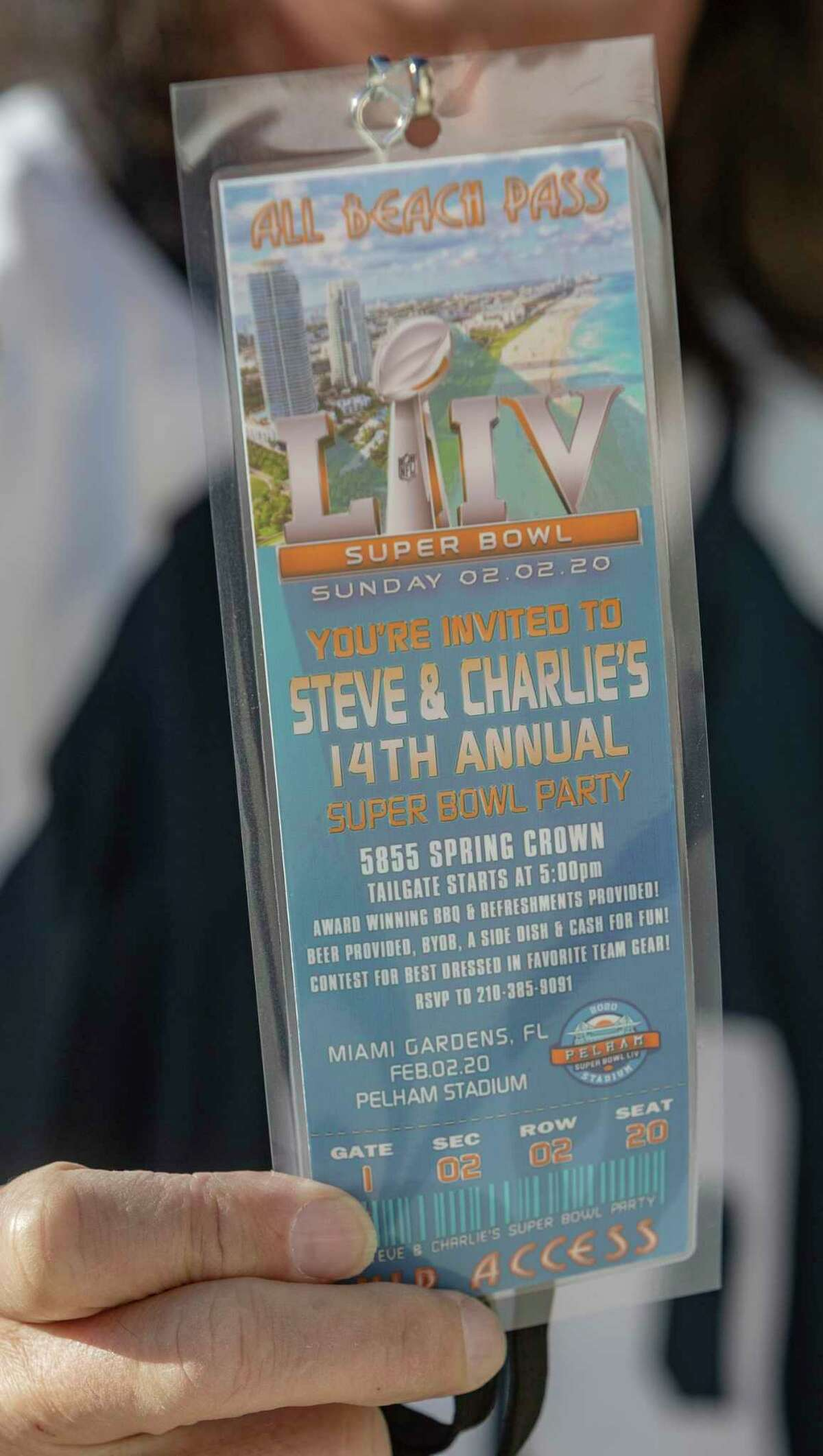 """Steve Pelham displays one of the """"tickets"""" a graphic designer friend made as an invitation to the 2020 neighborhood Super Bowl party he and his wife, Charlie, have hosted annually for 14 years. The Pelhams canceled it this year due to the coronavirus pandemic."""