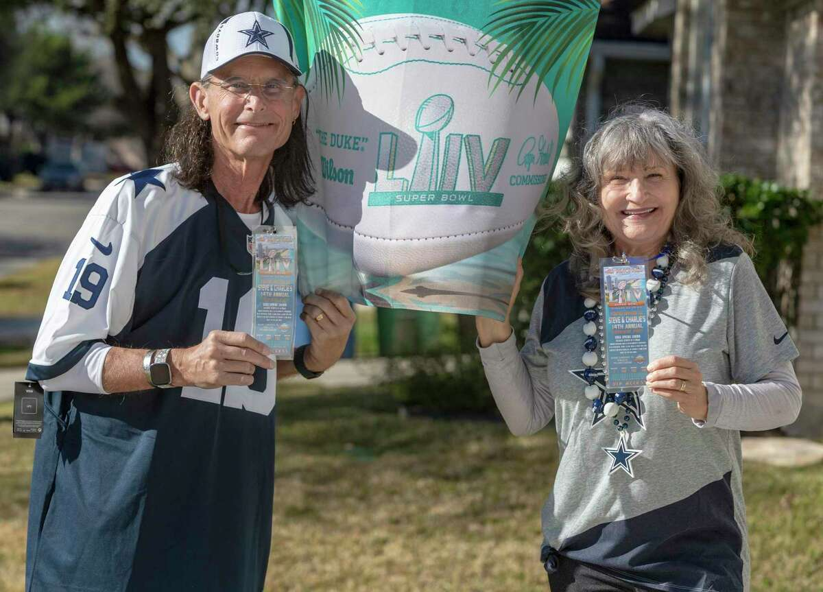 Steve and Charlie Pelham pose Wednesday outside their North Side home with some of the items from their 2020 Super Bowl party. The husband and wife had hosted the event for 14 years but canceled it this year due to the coronavirus pandemic.