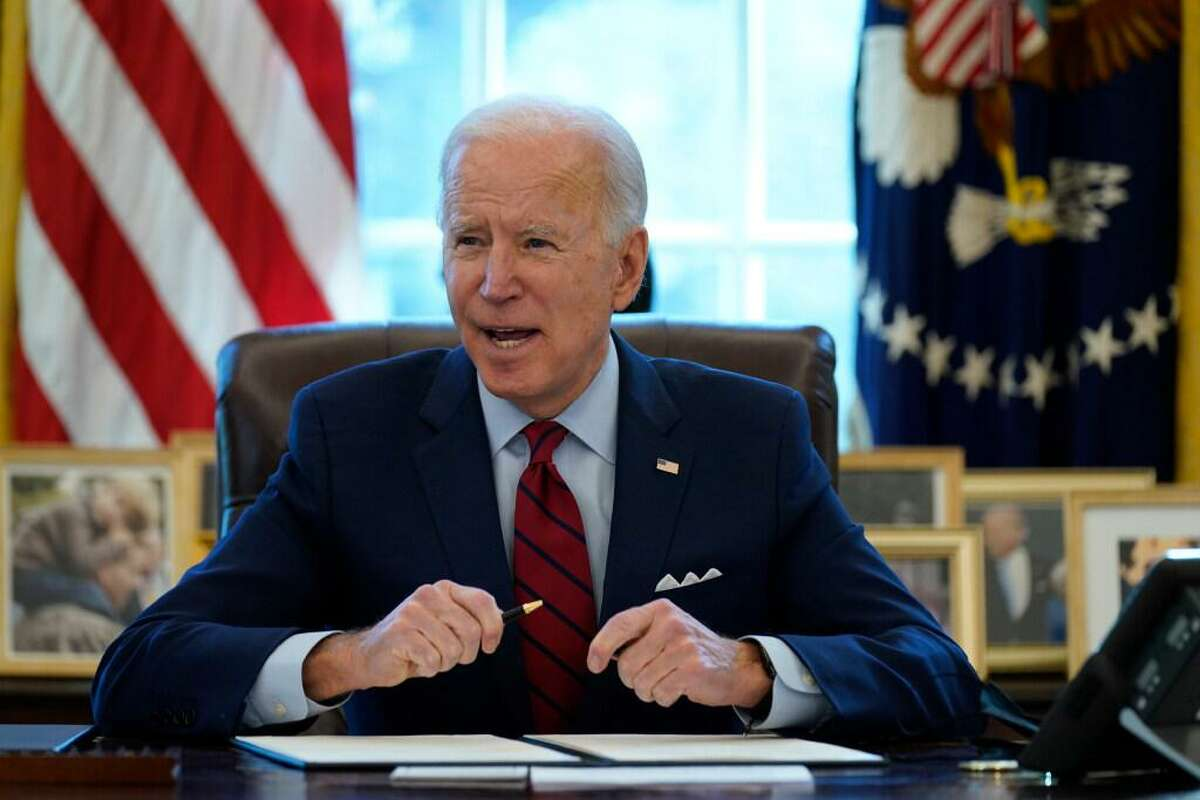 President Joe Biden signs a series of executive orders on health care, in the Oval Office of the White House, Thursday, Jan. 28, 2021, in Washington. The Democratic push to raise the minimum wage to $15 an hour has emerged as an early flash point in the push for a $1.9 trillion COVID relief package, providing an early test of President Joe Biden's ability to bridge Washington's partisan divide in pursuing his first major legislative victory.