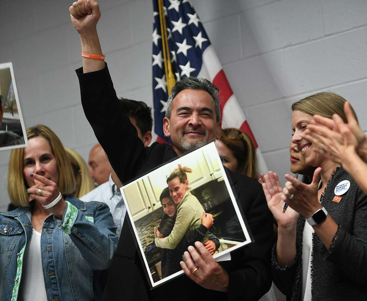 Standing with his wife Kristen, Michael Song, of Guilford, raises his fist in the air following the signing of Ethan's Law by Governor Ned Lamont in a ceremony at the Guilford Fire Department on Thursday, June 13, 2019. The Songs' son Ethan, 15, fatally shot himself with an unsecured gun in January of 2018.