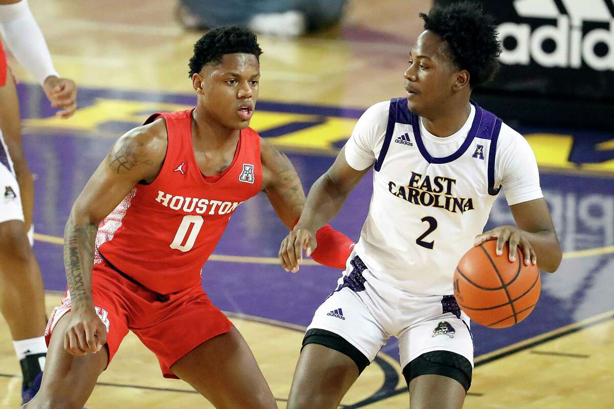 East Carolina's Tristen Newton (2) is challenged by Houston's Marcus Sasser (0) during the first half of an NCAA college basketball game in Greenville, N.C., Wednesday, Feb. 3, 2021. (AP Photo/Karl B DeBlaker)