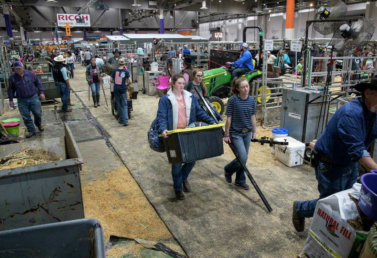 Taylor Barrett, center-left, carries her items out with her friend Amanda, center-right, after the Houston Livestock Show and Rodeo was cancelled due to concerns about COVID-19, on Wednesday, March 11, 2020, at NRG Center in Houston.