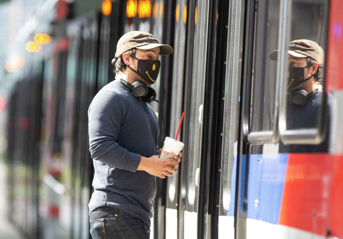 A Metropolitan Transit Authority rail passenger boards a train at the Main Street Square station on Feb. 3, 2021, in downtown Houston. Since June when masks became required on transit, Metro has handed out 2 million masks. That's expected to continue as a federal requirement for mask use kicked in earlier this week.