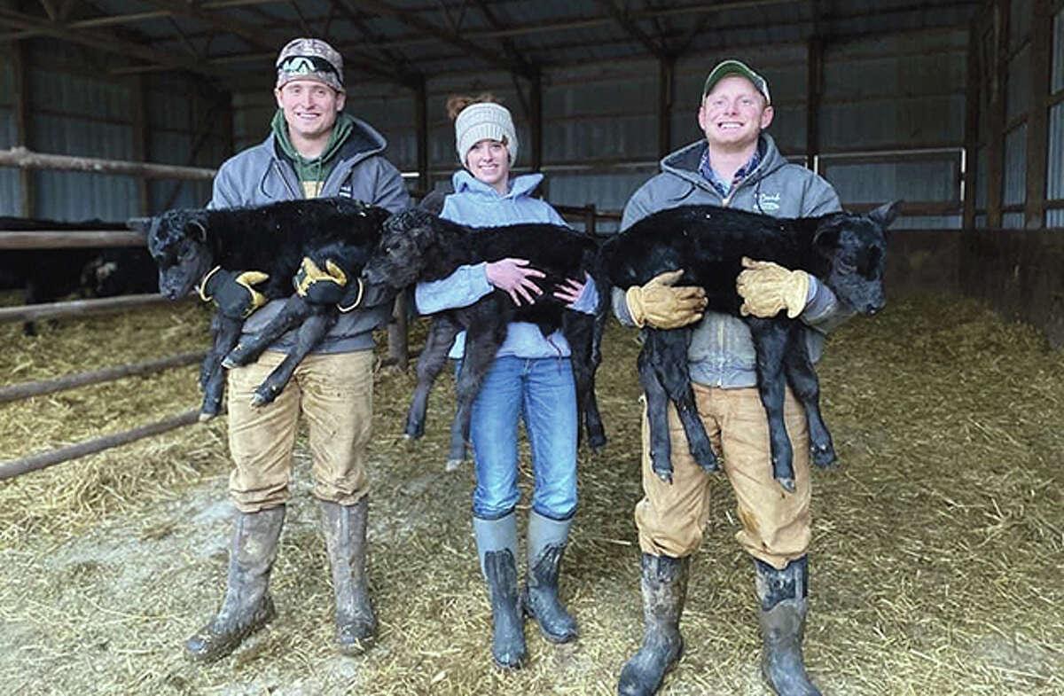 Ryan, Madeline and Joseph Ward - 23-year-old triplets - show off their triplet calves, born Jan. 24 on their farm near Rushville.