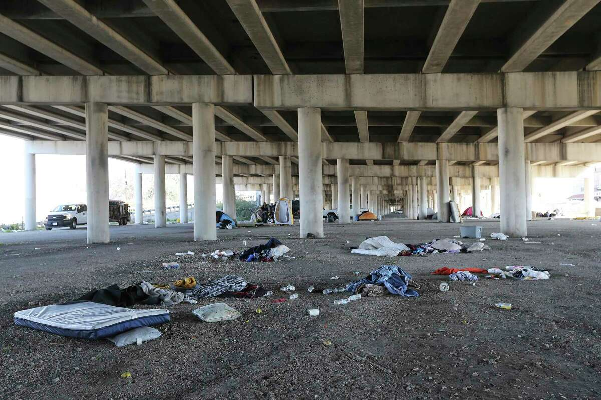 Piles of debris left behind are seen under the highway in downtown San Antonio where nearly 100 people who are homeless and had set up camp were removed by city crews Wednesday.
