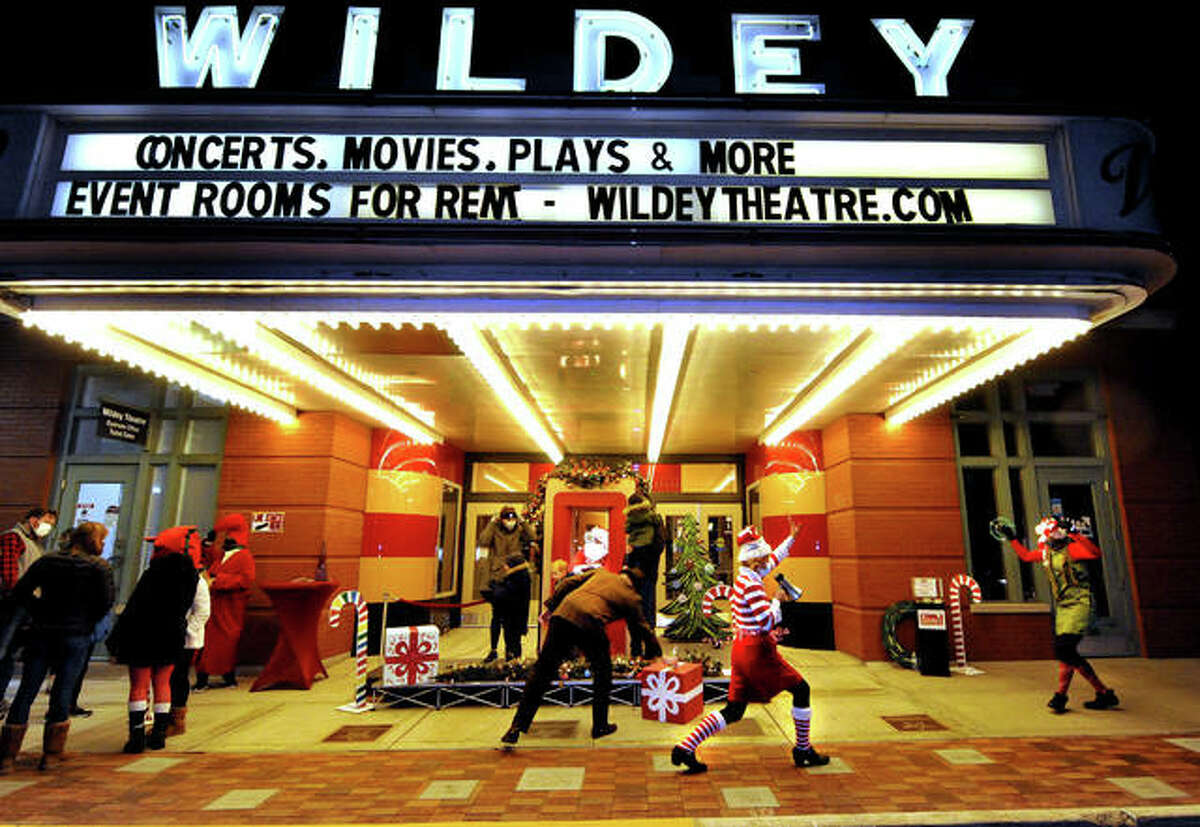 In this Dec. 18, 2020 file photo, Santa's elves dance around as children visit him in the ticket booth of the Wildey Theater on Main Street. Because of social distancing due to the coronavirus pandemic, Santa had to stand behind a glass to greet children.